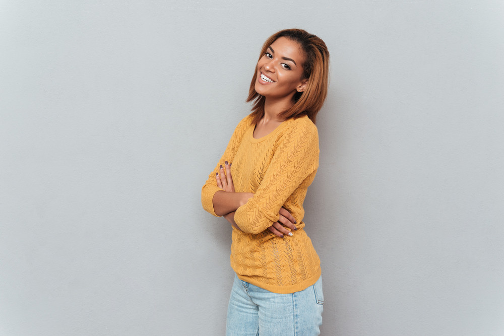 Young happy african woman in yellow sweater and jeans standing sideways with arms crossed and looking at camera. Isolated gray background