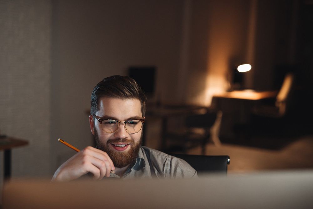 Young happy bearded web designer dressed in shirt working late at night and looking at computer.