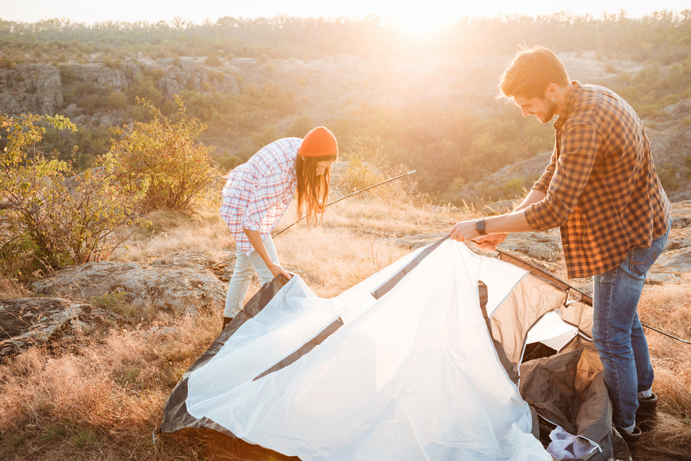 Young happy couple setting up a tent outdoors