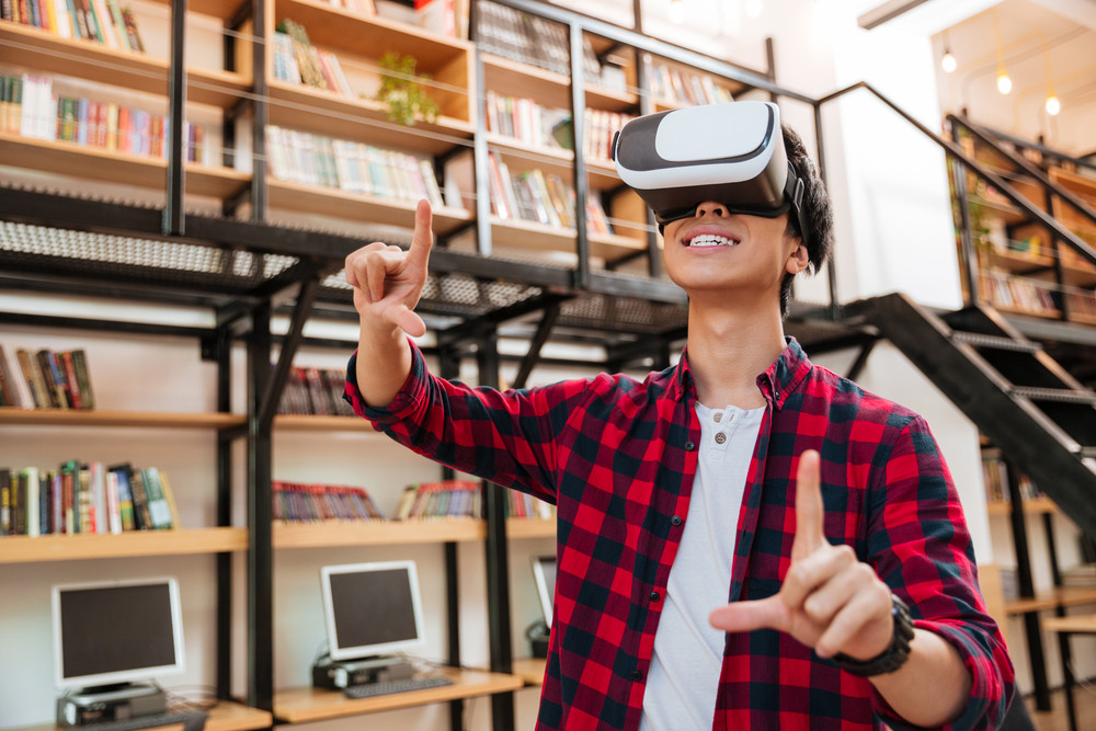 Young happy man dressed in casual shirt in a cage and wearing virtual reality device in the library.