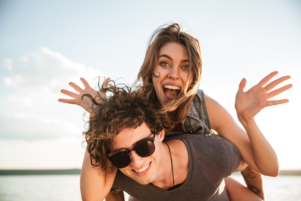 Young happy smiling couple in love piggyback at the beach, cheerful girl is screaming