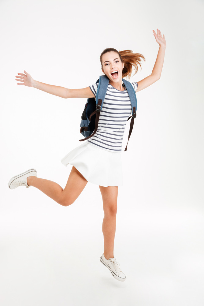 Young happy woman with backpack jumping and celebrating success isolated on a white background