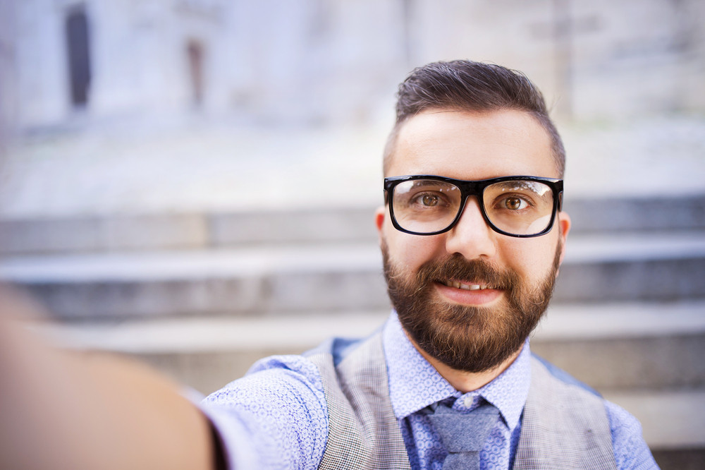 Young hipster businessman taking selfie in city street