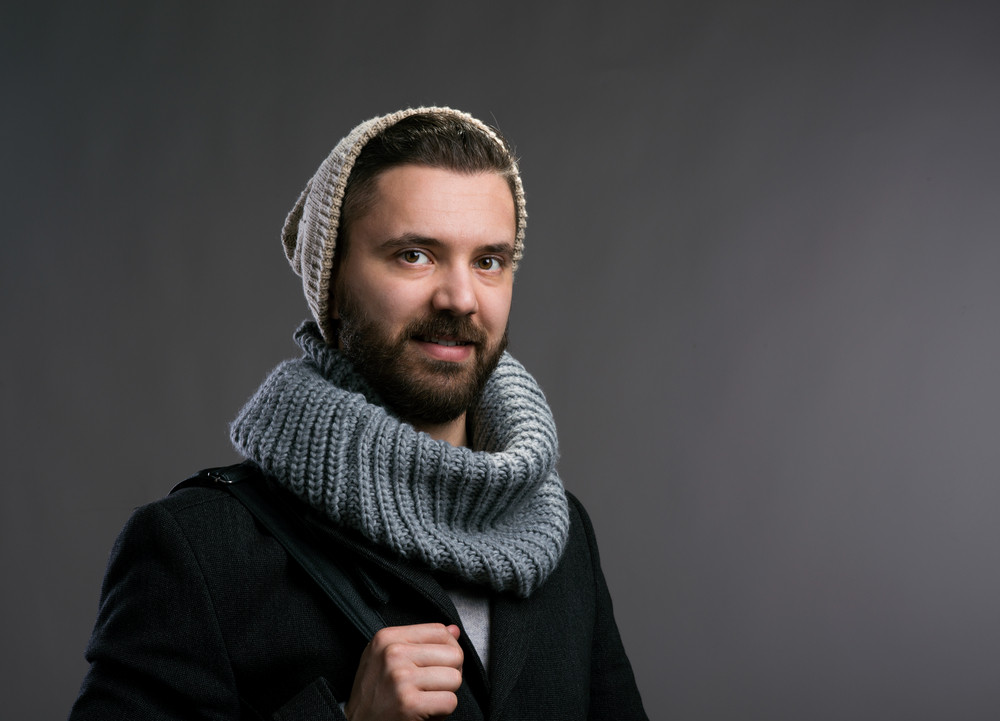 Young hipster man in black winter coat, knitted scarf and beanie. Studio shot on gray background.