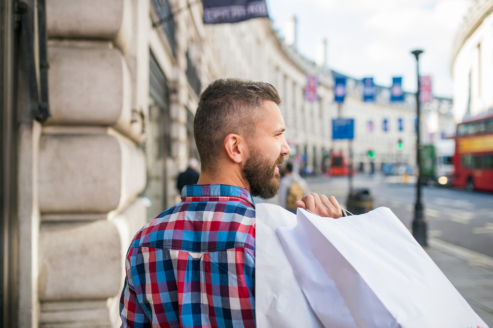 Young hipster man in checked shirt shopping, holding bags, in the streets of London, back view, rear viewpoint