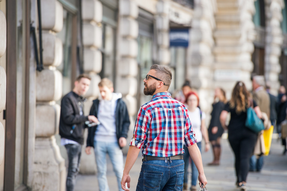 Young hipster man in checked shirt shopping in the streets of London, back view, rear viewpoint