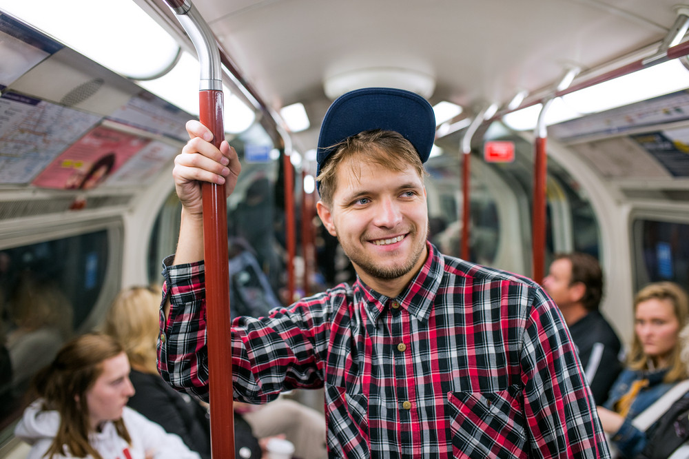 Young hipster man in checked shirt standing in a crowded subway train