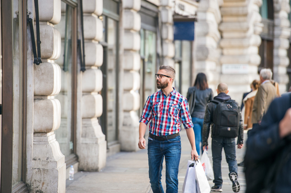 Young hipster man with eyeglasses in checked shirt shopping, holding a bag, in the streets of London
