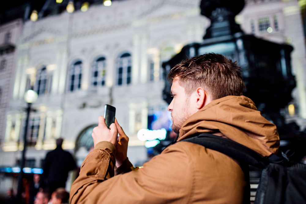 Young hipster man with smart phone, taking picture, walking in the streets of London at night