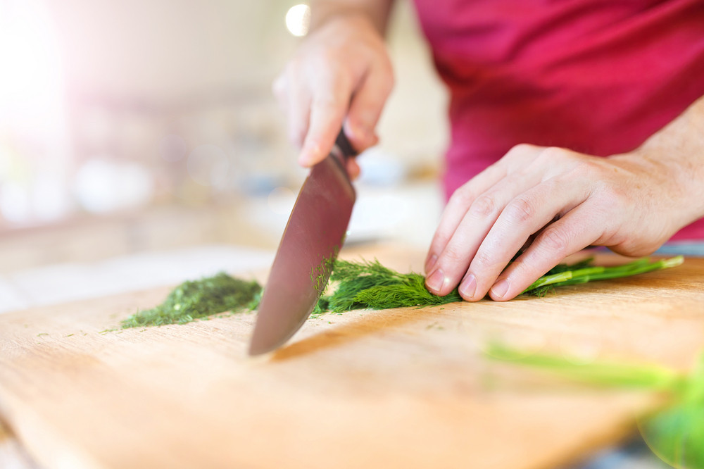 Young man cutting dill in his domestic kitchen