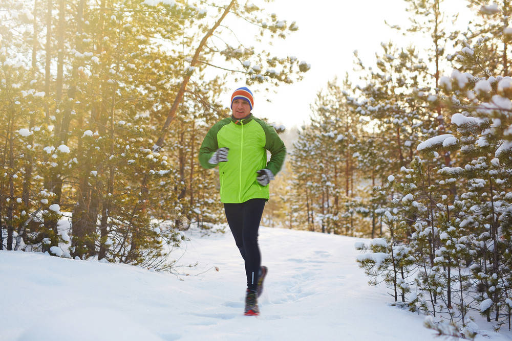 Young man in active-wear running in winter forest