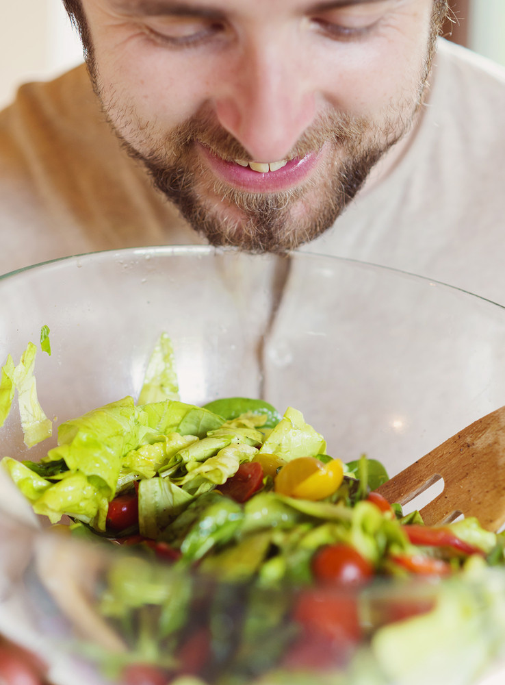 Young man in the kitchen preparing green salad