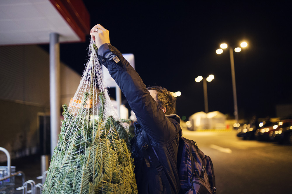 Young man in town buying a christmas tree