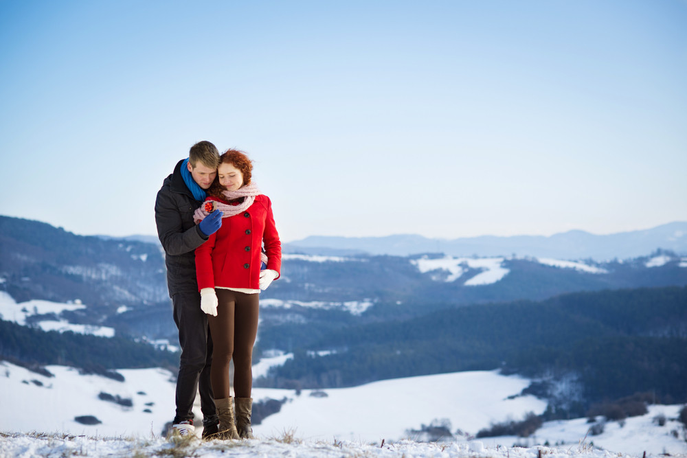Young man is asking to married a beautiful girl in snow country.