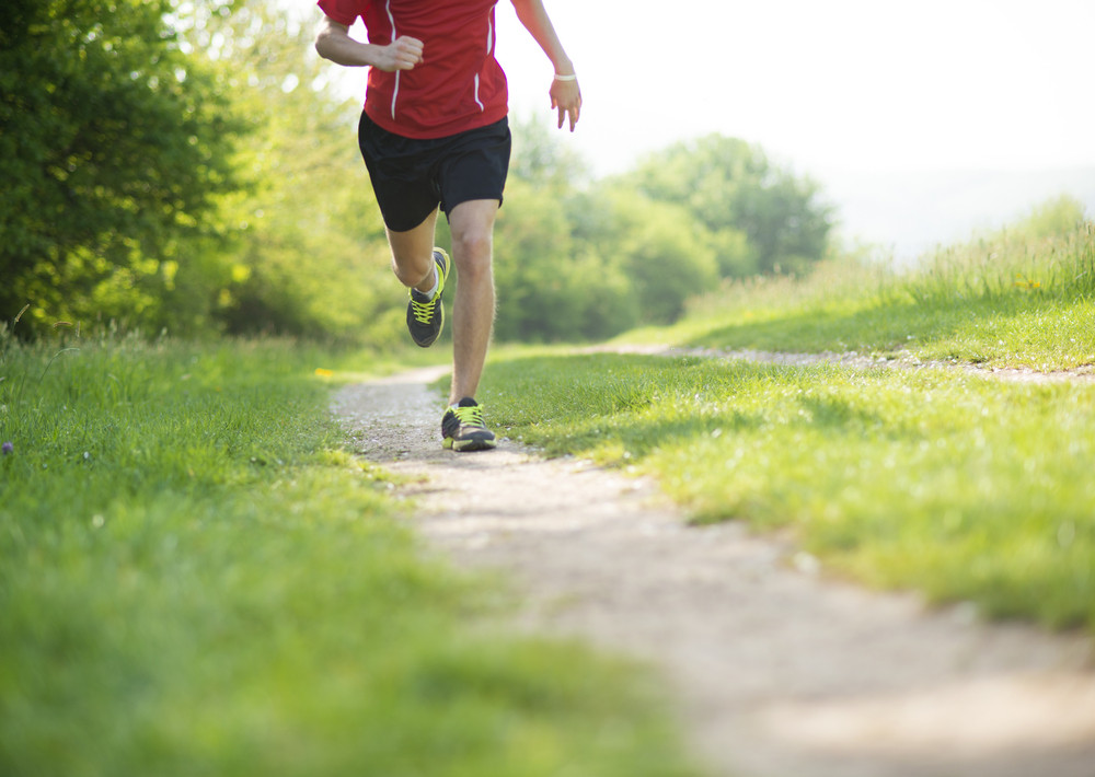 Young man is running in sunny nature