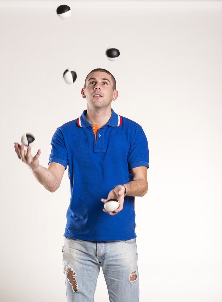 Young man juggling with several balls at once