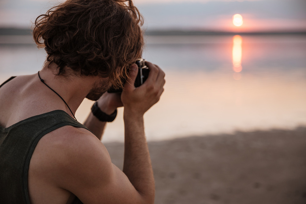 Young man making photo of sunset with camera outdoors