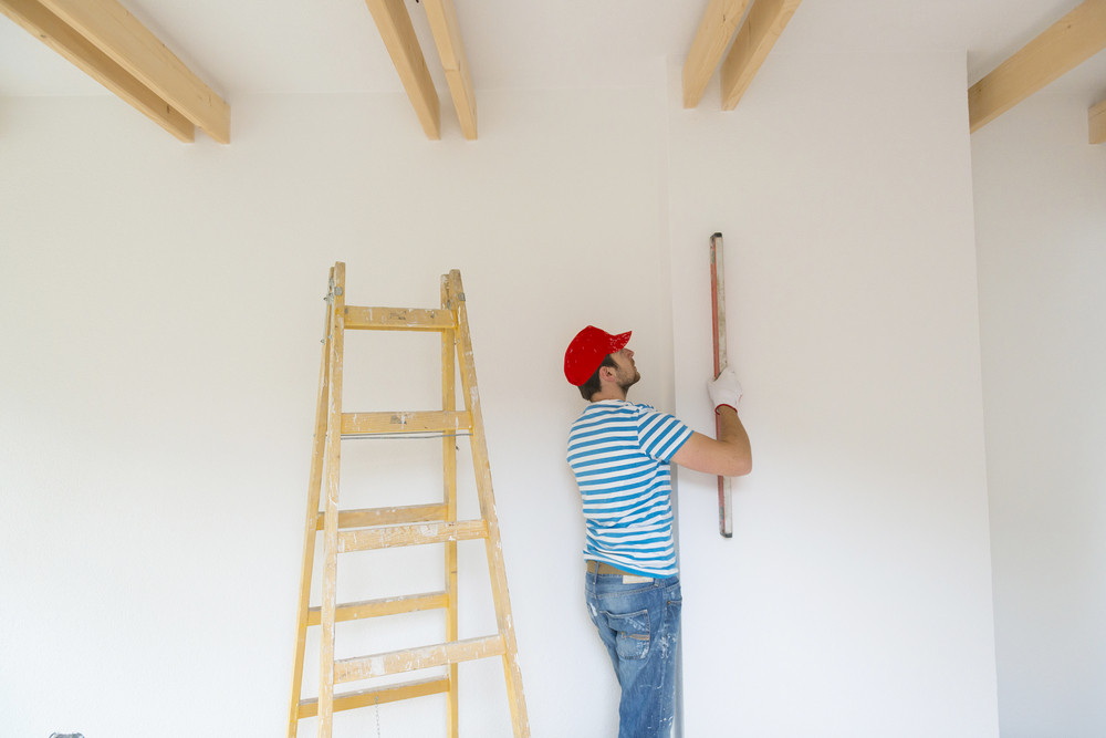 Young man measuring the wall of new home with level