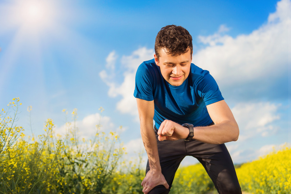 Young man running outside in spring canola field