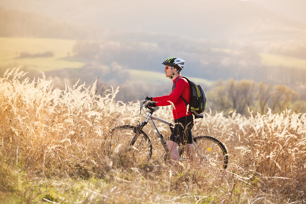 Young man takes a break in a field while mountain biking