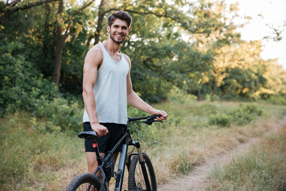 Young man with bicycle on forest road looking at camera.