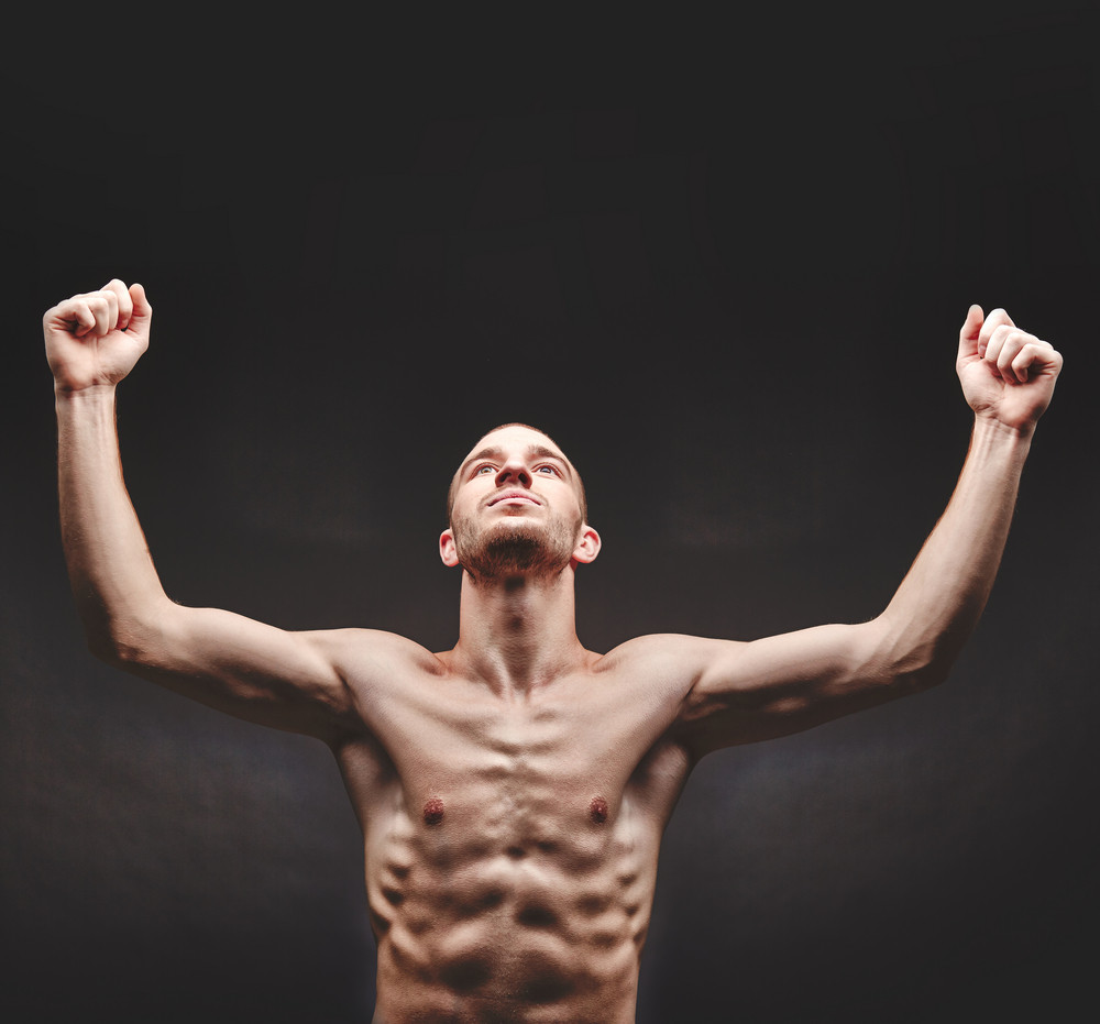 Young man with raised arms in isolation