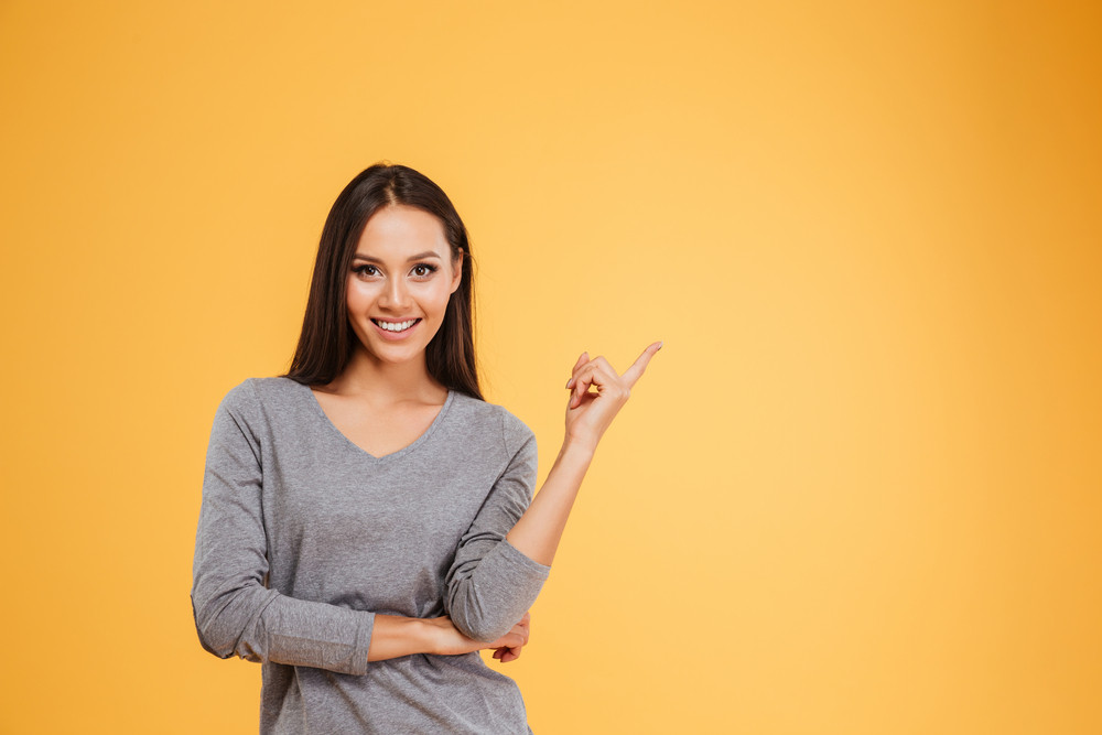 Young model pointing upwards in studio. isolated orange background