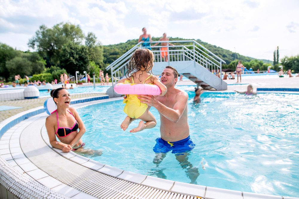 Young mother and father lifting up their daughter in inflatable ring in swimming pool in aqua park. Summer heat and water.