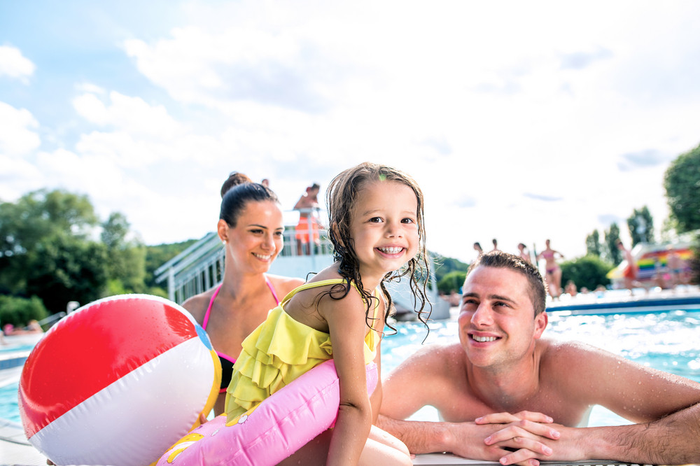 Young mother and father with their daughter in inflatable ring in swimming pool in aqua park. Summer heat and water.
