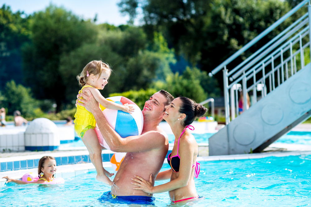 Young mother and father with their daughter in the arms in swimming pool in aqua park. Summer heat and water.