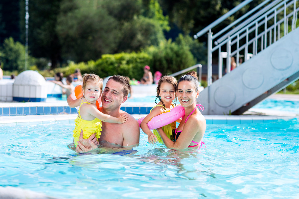 Young mother and father with their daughters in the arms in swimming pool in aqua park. Summer heat and water.