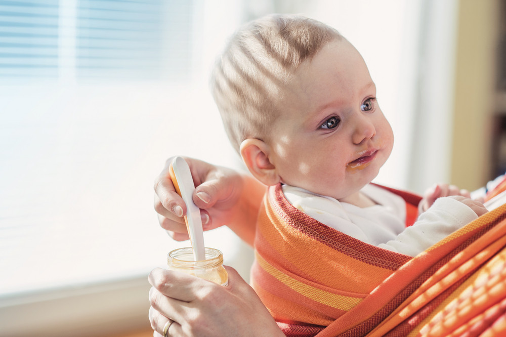 Young mother feeding her little daughter that she has in a baby carrier