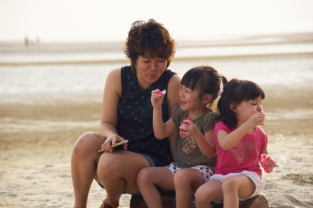 Young mother making soap bubbles with two happy kids around