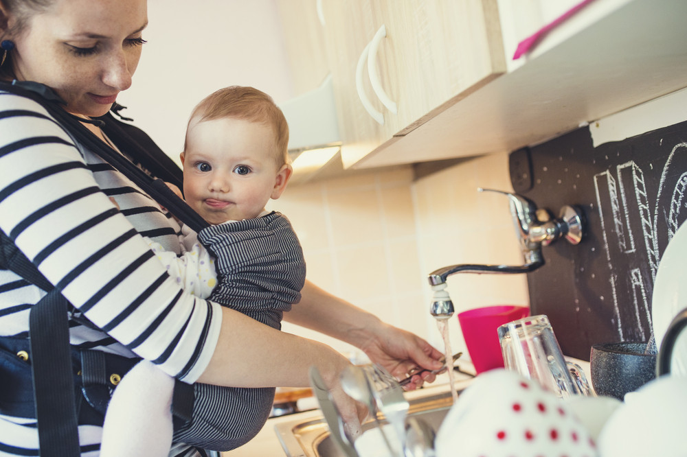 Young mother washing up dishes with her little daughter that she has in a baby carrier