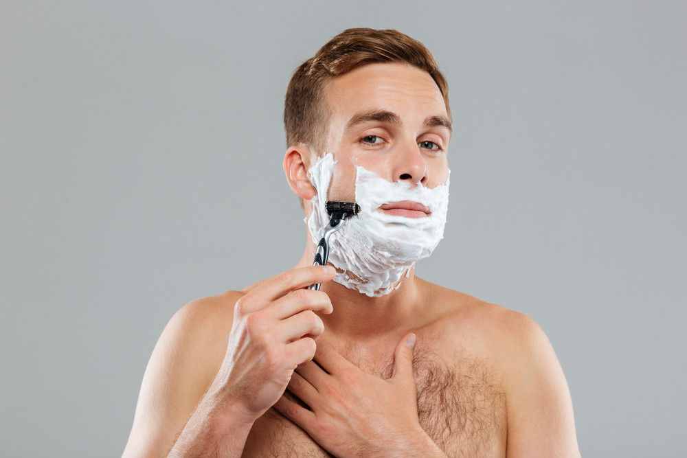 Young muscular man shaving over gray background and looking at camera