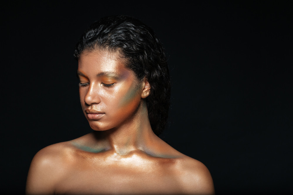 Young naked african woman in studio. isolated black background