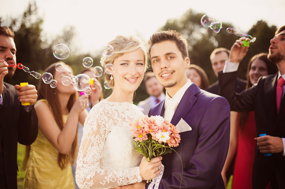Young newlyweds enjoying romantic moment together at wedding reception outside, wedding guests in background blowing bubbles