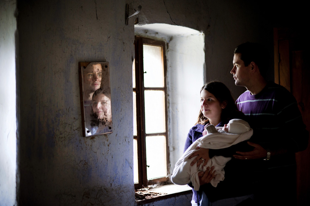 Young parents with little baby boy in the old house