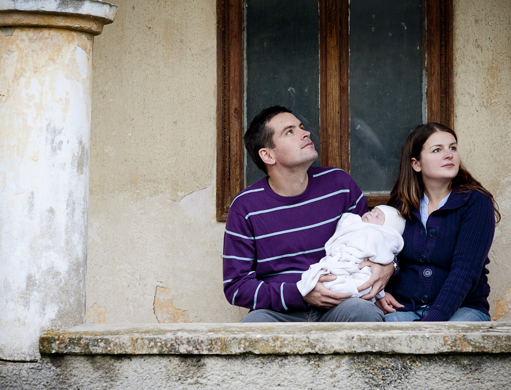 Young parents with little baby boy outside the old house