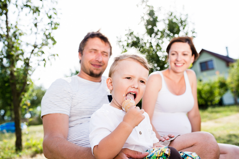 Young parents with their little son eating ice cream, sunny summer garden