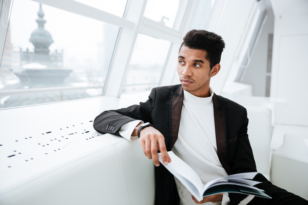 Young Pensive african business man in black suit sitting on white sofa and holding journal in office