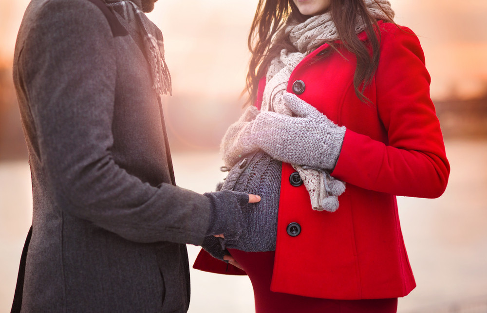 Young pregnant couple portrait in winter town