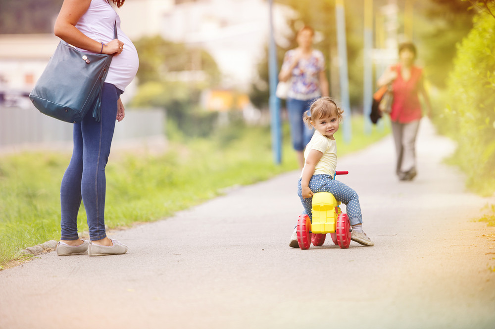 Young pregnant mother with her little daughter on small motorbike spending time together in park