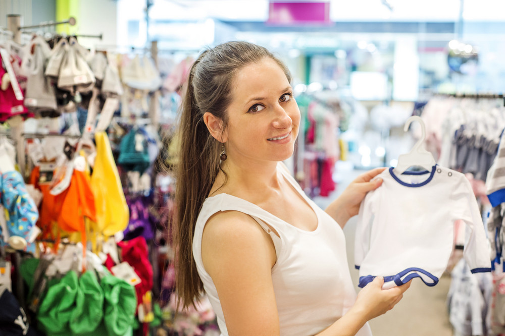 Young pregnant woman choosing baby clothes at baby shop store