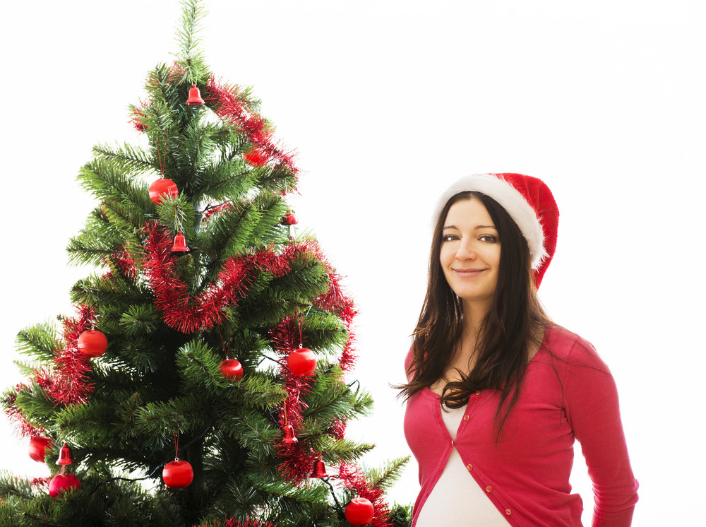 Young pregnant woman is decorating christmas tree.