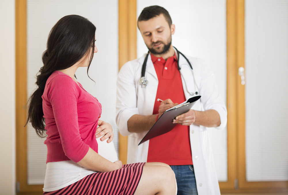 Young pregnant woman with doctor in hospital.