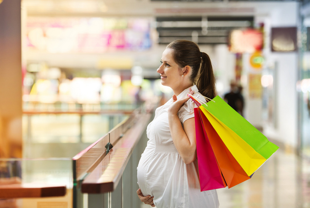 Young pregnant woman with shopping bags in shopping mall