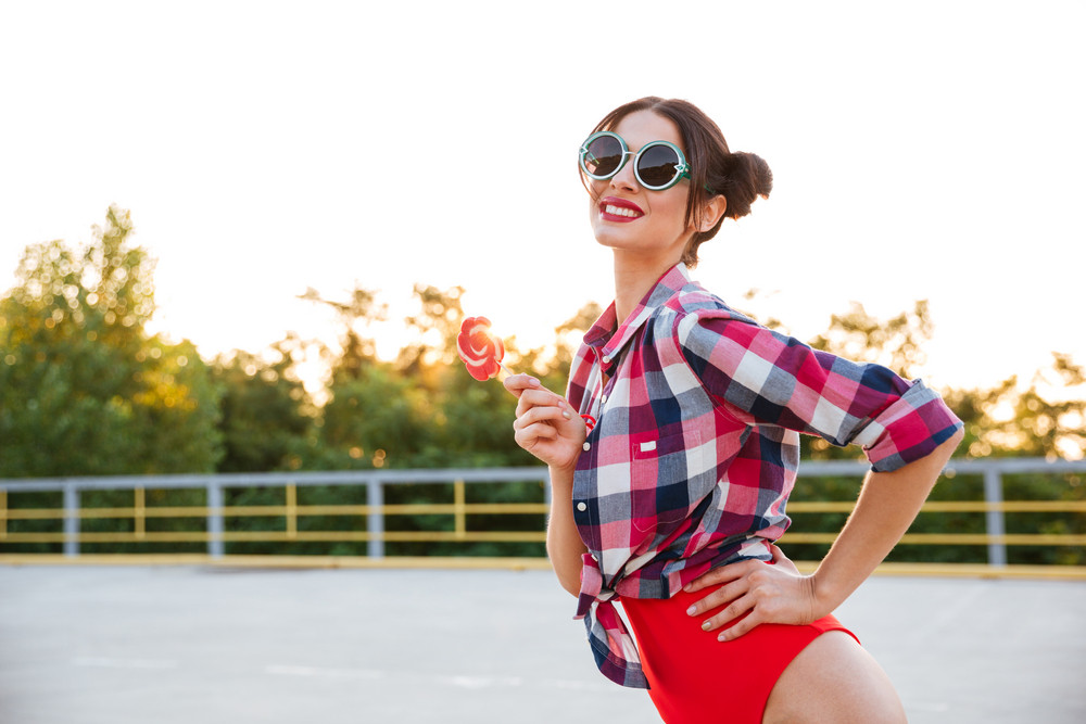 91ea2fba1a Young pretty brunette girl in sunglasses and red swimsuit posing and  holding lollipop on the open