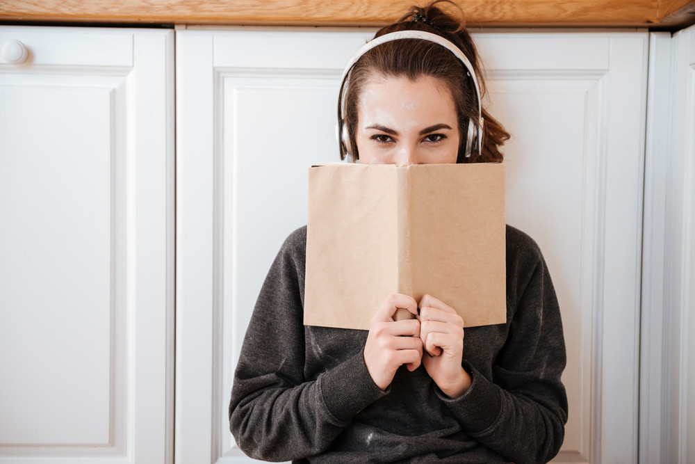 Young pretty girl in headphones covering face with book in the kitchen at home