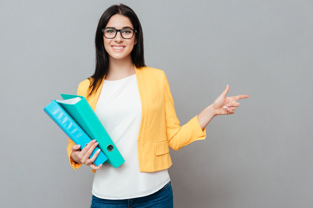 Young pretty woman wearing eyeglasses and dressed in yellow jacket holding folders and ponting to copyspace over grey background.